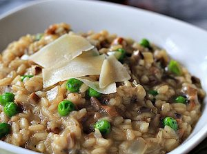 Italian Mushroom and Pea Risotto garnished with shaved Parmesan cheese