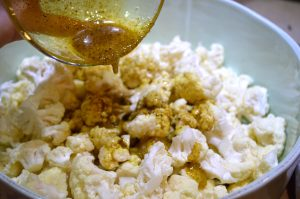 Adding Curry and lemon mixture to Cauliflower for Curry Roasted Cauliflower found in post titled 'Achcha Khana (Good Food)'